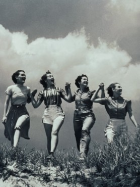 four-women-walking-in-a-line-holding-hands